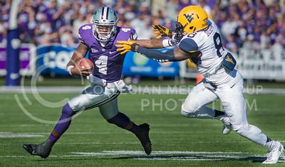 Photo by Emily DeShazer | The Collegian  Sophomore quarterback Daniel Sams stiff arms West Virginia sophomore safety Karl Joseph on Saturday Oct. 26 at Bill Snyder Family Stadium.