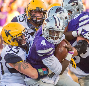 Photo by Emily DeShazer | The Collegian  Sophomore quarterback Daniel Sams keeps his eyes down field as he's tackled by West Virginia junior linebacker Jared Barber on Saturday Oct. 26 at Bill Snyder Family Stadium.