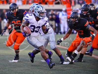 (Photo by Parker Robb |  Collegian)  K-State running back John Hubert attempts to circumnavigate OSU safety Lyndell Johnson during the Wildcats' last grasp at a win over the Oklahoma State Cowboys Saturday afternoon in Stillwater, Oklahoma. After getting a first down, quarterback Daniel Sams' pass was intercepted to seal the Cowboys' 33-29 victory.