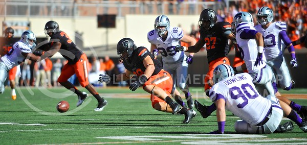 (Photo by Parker Robb |  Collegian)  K-State and Oklahoma State players dive for a loose ball fumbled by K-State defensive end Laton Dowling on his kickoff return at the end of the first half of the Wildcats' game against Oklahoma State in Stillwater, Oklahoma, Saturday afternoon. The fumble was eventually ruled an illegal forward pass, and after the penalty, K-State kneeled on two plays to end the first half down by three, 17-14. The Wildcats' game was marred by an unusually-high twelve penalties and five turnovers.