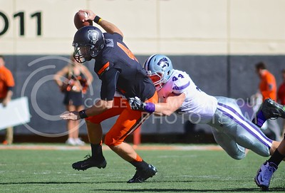 (Photo by Parker Robb |  Collegian)  K-State defensive end Ryan Mueller attempts to tackle OSU quarterback J.W. Walsh during the second quarter of the Wildcats' game against Oklahoma State in Stillwater, Oklahoma, Saturday afternoon. The Cowboys beat the Wildcats 33-29 in a tense game that went down to the wire, sealing their win with an interception with eighteen seconds remaining.
