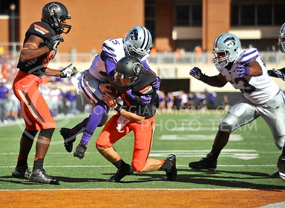(Photo by Parker Robb |  Collegian)  K-State defensive back Randall Evans tackles OSU quarterback J.W. Walsh as he stumbles into the end zone for a touchdown at the end of the second quarter of the Wildcats' game against Oklahoma State in Stillwater, Oklahoma, Saturday afternoon. The Cowboys beat the Wildcats 33-29 in a tense game that went down to the wire, sealing their win with an interception with eighteen seconds remaining.