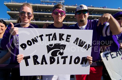 "Photo by Jed Barker | The Collegian  K-State fans hold up a sign in support of keeping the tradition of Willie the Wildcat tackling a ""fan"" of the opposing team as part of the football pre-game show.  The tradition seems to have been stopped after the ""fan"" suffered a head injury after being tackled during the show before the game against West Virginia on October 26, 2013."