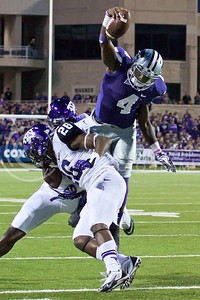Photo by Jed Barker | The Collegian  K-State sophomore quarterback Daniel Sams leaps over TCU strong safety Derrick Kindred to get the first down at Bill Snyder Family Stadium on November 16, 2013.