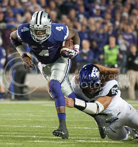 (Photo by Taylor Alderman / The Collegian)  Sophomore quarterback Daniel Sams is held onto by TCU sophomore defensive end Mike Tuaua on Nov. 16, 2013 at Bill Snyder Family Stadium.