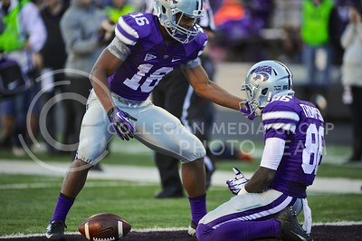 (Photo by Parker Robb | Collegian)  Junior wide receiver Tyler Lockett congratulates senior wide receiver Tramaine Thompson after catching a 27-yard pass on the 3-yard line in the fourth quarter of the Wildcats' win over the Iowa State Cyclones Saturday afternoon in Bill Snyder Family Stadium. The next play, senior running back John Hubert ran the ball three yards for a touchdown to put K-State up 27-0.
