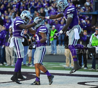 (Photo by Parker Robb | Collegian)  Senior running back John Hubert (33) is congratulated by senior wide receiver Torell Miller (88) and sophomore quarterback Daniel Sams (4) after his 3-yard touchdown run in the fourth quarter of the Wildcats' win over the Iowa State Cyclones Saturday afternoon in Bill Snyder Family Stadium. Hubert ran the ball fifteen times for a total of 107 yards and two touchdowns, and continues to move up the ranks of the top-ten K-State rushers.