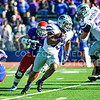 Then-junior KU linebacker Ben Heeley (31) chases down Then-senior K-State runningback John Hubert (33) as Hubert finds and exploits a hole in KU's defense during the 2013 Sunflower Showdown November 30 at Memorial Stadium in Lawrence. (Parker Robb | The Collegian)