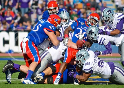 (Photo by Parker Robb | Collegian)  K-State and KU players dive for a loose ball dropped by KU running back James Sims, which would be recovered by sophomore defensive back Dante Barnett, during the second quarter of the annual Sunflower Showdown Saturday in Memorial Stadium in Lawrence. The Wildcats beat the Kansas Jayhawks 31-10 in a back-and-forth game characterized by many turnovers. The Jayhawks surrendered six turnovers, while the Wildcats had two. The governor's cup, awarded to the winner of the intrastate rivalry each year, returns to K-State for the fifth year in a row.