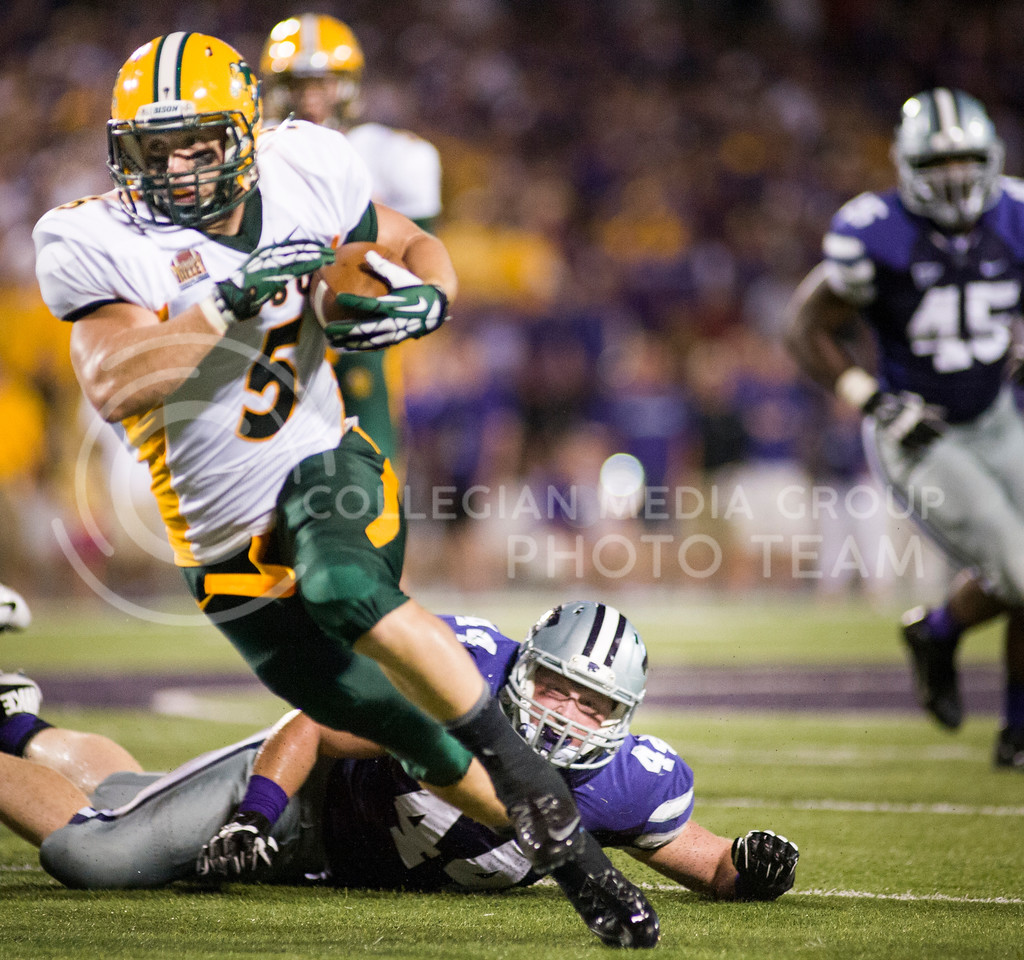 (Photo by Emily DeShazer / The Collegian)<br /> North Dakota State running back Derrick Lang runs out of reach of a K-State defender on Aug. 30, 2013.