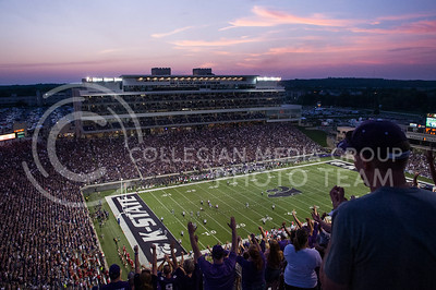 (Photo by Emily DeShazer / The Collegian) The sunset lights up the sky behind Bill Snyder Family Stadium as Ty Zimmerman returns a 32 yard interception for a touchdown on Aug. 7, 2013.