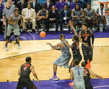 (Photo by Emily DeShazer | Collegian)  K-State junior forward Thomas Gipson passes the ball out to freshman forward Wesley Iwundu on Jan. 4 at Bramlage Coliseum during the 74-71 win over No. 6 Oklahoma State.