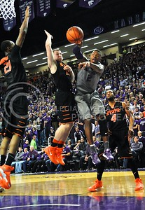 (Photo by Parker Robb | Collegian)  Freshman forward Marcus Foster jumps toward the basket like he is going to take a shot, but instead passes the ball across the baseline to a teammate for an assist in the first half of the Wildcats' 74-71 upset victory over the #6-ranked Oklahoma State Cowboys in Bramlage Coliseum January 4, 2014.