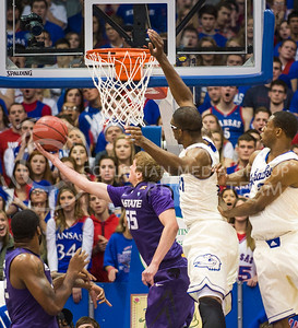 (Photo by Emily DeShazer | The Collegian)  K-State senior guard Will Spradling lifts in a lay up freshman center Joel Embiid on Jan. 11 at Allen Fieldhouse.