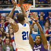 (Photo by Emily DeShazer | The Collegian)  Kansas freshman center Joel Embiid shoots a three over K-State sophomore forward D.J. Johnson on Jan. 11 at Allen Fieldhouse.