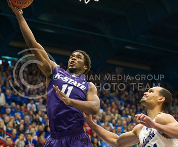 (Photo by Emily DeShazer | The Collegian)  K-State junior forward Nino Williams lays in a basket as Kansas sophomore Perry Ellis watches on Jan. 11 at Allen Fieldhouse.
