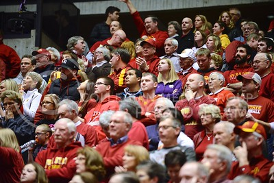 (Photo by Parker Robb | Collegian)  A lone K-State fan in the midst of a sea of red- and yellow-clad Cyclones fans watches in discouragement as Iowa State extends their lead in the final minute solely on free throws, going on to beat the K-State Wildcats 81-75 in Hilton Coliseum in Ames, Iowa, January 25, 2014.