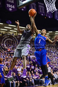 (Photo by Parker Robb | Collegian)  Senior guard Omari Lawrence takes a layup as Kansas freshman guard Wayne Selden, Jr., attempts to block it in the second half of K-State's 85-82 overtime upset victory over the #7-ranked Jayhawks in the 279th Sunflower Showdown February 10, 2014, in Bramlage Coliseum. (Photo by Emily DeShazer | The Collegian)