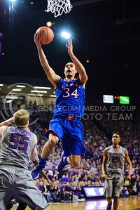 (Photo by Parker Robb | Collegian)  Kansas sophomore forward Perry Ellis goes over senior guard Will Spradling for a layup in the first half of K-State's 85-82 overtime upset victory over the #7-ranked Jayhawks in the 279th Sunflower Showdown February 10, 2014, in Bramlage Coliseum.