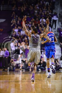 (Photo by Parker Robb | Collegian)  Senior guard Omari Lawrence runs down the court with arms raised after making a difficult shot amidst swarming defenders in the second half of K-State's 85-82 overtime upset victory over the #7-ranked Jayhawks in the 279th Sunflower Showdown February 10, 2014, in Bramlage Coliseum. (Photo by Emily DeShazer | The Collegian)