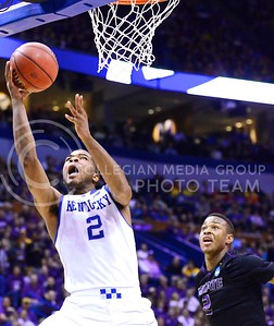 Parker Robb | The Collegian  Kentucky freshman guard Aaron Harrison circumvents K-State freshman forward Marcus Foster and goes for a layup in the second half of the Kentucky Wildcats' victory over the K-State Wildcats in the NCAA Tournament Second Round in St. Louis March 21, 2014.