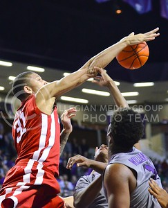 (Photo by Parker Robb   Collegian)  Oklahoma forward D.J. Bennett blocks a K-State shot during the second half of the Wildcats' 72-66 victory over the #25 Oklahoma Sooners January 14, 2014, in Bramlage Coliseum. The Sooners and Wildcats would remain neck-and-neck until K-State pulled away in the final minutes off free throws from Nino Williams.
