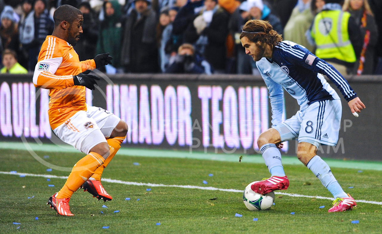(Photo by Parker Robb | Collegian)<br /> <br /> Sporting KC midfielder Graham Zusi attempts to advance the ball past Houston Dynamo defender Corey Ashe during the MLS Eastern Conference championship game November 23 at Sporting Park, where Kansas City beat Houston 2-1. Sporting KC has had a championship-caliber season, amassing a 17-10-7 record, most recently avenging the club's two losses to Houston in the Eastern Conference championship games the previous two years, and now hosting the MLS Cup on December 7.