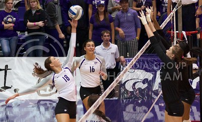 Photo by Jed Barker | The Collegian  Senior, outside hitter Courtney Traxson attempts to tip the ball over the Texas Longhorns blockers at Ahearn Field House on October 26, 2013.
