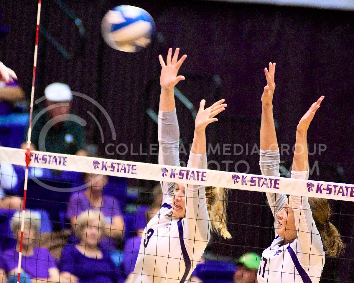 (Photo by Jed Barker | Collegian)<br /> Redshirt junior, outside hitter  Chelsea Keating (left) and senior middle blocker Kaitlynn Pelger (right) raise their arms up and attempt to block the spiked ball as it flies over the net.  The Wildcats played against the Italian U-23 National Team at Ahearn Field House on September 24, loosing the 5 set match after struggling in the last three sets.