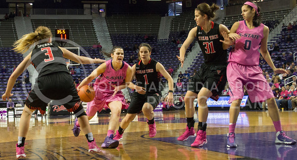(Photo by Taylor Alderman | Collegian)   Leticia Romero, freshman guard, drives through raider defense of Minta Spears and Marina Lizarazu while Haley Schneider defends Jessica Sheble. The cats defeated the raiders 60-54 on February 15, 2014 at Bramlage Coliseum.