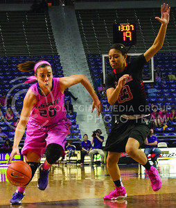 (Photo by Taylor Alderman | Collegian)   Bri Craig, sophomore guard, dribbles past Jasmine Caston. The cats defeated the raiders 60-54 on February 15, 2014 at Bramlage Coliseum.