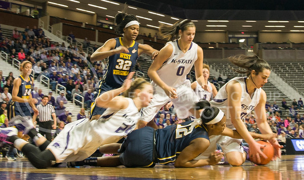 (Photo by Emily DeShazer | The Collegian)  Wildcats and Mountaineers dive for a loose ball during K-State's 61-40 loss to West Virginia Saturday in Bramlage Coliseum.
