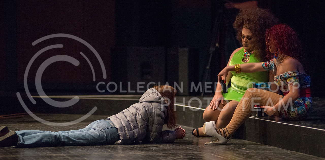 An attendee of the 11th-annual K-State Drag Show shows Victoria Fox and Monica Moree a picture from the previous year's drag show to win a prize during the opening of the drag show on Feb. 20, 2015 in McCain Auditorium. (George Walker | The Collegian)
