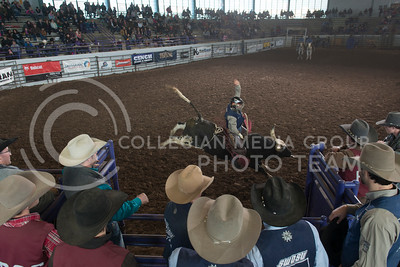 Rodeo athletes and officials watch from behind the gates as Mickey Andrews, from Southwestern Oklahoma State University, trys his best to stay on during the bull riding finals at Sundays K-State Rodeo. (Evert Nelson | Collegian)
