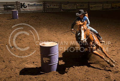 Jordyn Eddington, from Garden City Community College, rides her horse cafeful not to hit the barrel during the barrel racing event at Fridays K-State Rodeo at Weber Arena. (Evert Nelson | Collegian)