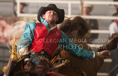 Logan Patterson, of Oklahoma Panhandle State University, rides a bucking bronco during the bareback competition at Sundays KSU Rodeo. The 59th annual event, organized by K-State Rodeo, was held at Weber Arena from Friday through Sunday. (Evert Nelson | Collegian)