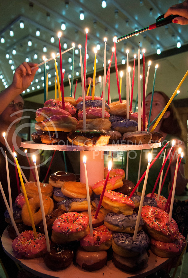 Volunteers light 125 candles on a giant donut cake made by Varsity Donuts for the Aggieville 125th anniversary celebration in front of Varneys on Saturday night, Sept. 20, 2014. (Hannah Hunsinger | The Collegian)