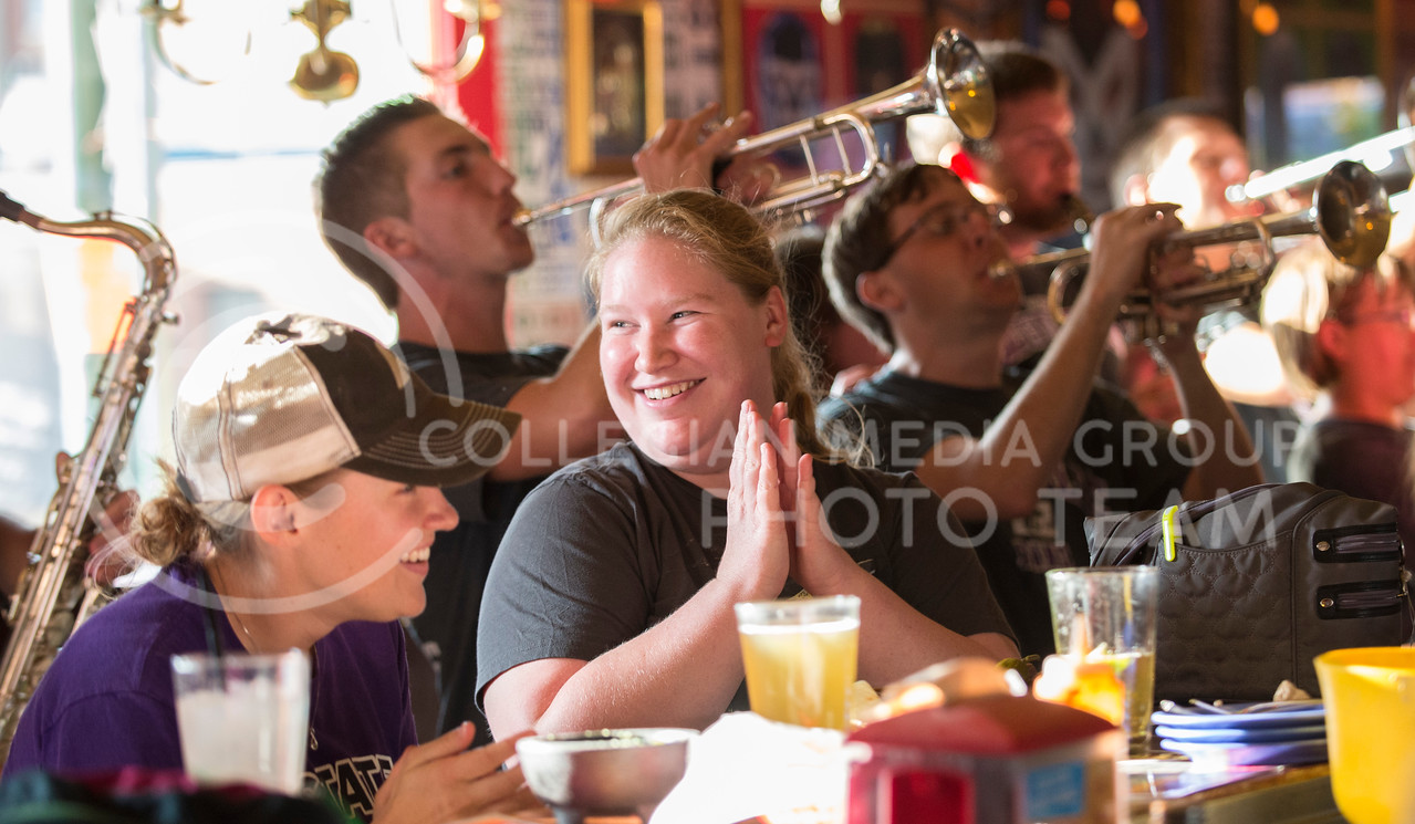 Patrons at Taco Lucha clap along to the Wabash as members of the K-State marching band perform for the Aggieville 125th anniversary celebration onSaturday, Sept. 20, 2014. (Hannah Hunsinger | The Collegian)