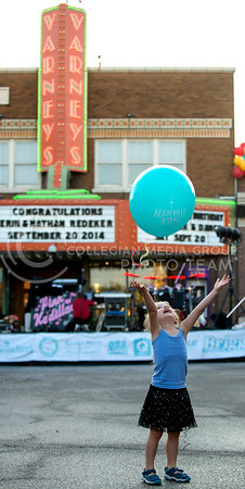 Millicent Sanderson, 3, of Manhattan, plays with a ballon on Moro St. before the evening festivities for the Aggieville 125th anniversary celebration on Saturday night, Sept. 20, 2014. (Hannah Hunsinger | The Collegian)