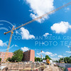 A massive crane towering over the Wefald Hall construction site lifts a vat of concrete from a truck to workers waiting to spread it in the foundation of the new building June 26, 2015. (Parker Robb | The Collegian)