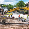 Workers spread concrete for the pedestrian mall being installed between the power plant, Seaton Hall and Rathbone Hall June 26, 2015. (Parker Robb | The Collegian)