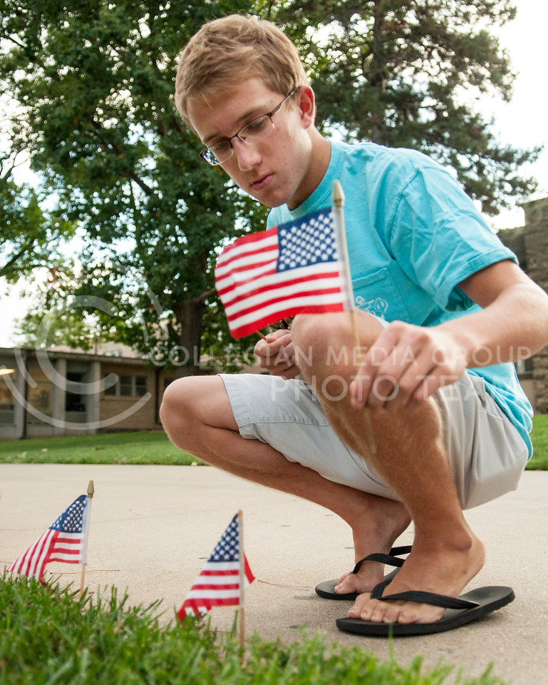 "Kyle Becher, sophmore in finance, places flags in the quad for 9/11 on Wednesday evening, Sept. 10, 2014.  Becher was volunteering for fraternity hours for Delta Sigma Phi and to ""give back to the university."" (Hannah Hunsinger 