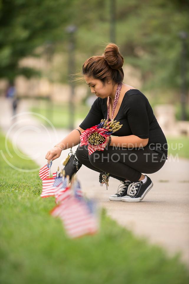 Rochelle Visitacion, freshman in journalism, volunteers her time to decorate the quad for a 9/11 memorial  and to remember her husband, who is currently deployed on Wednesday evening, Sept. 10, 2014. (Hannah Hunsinger | The Collegian)