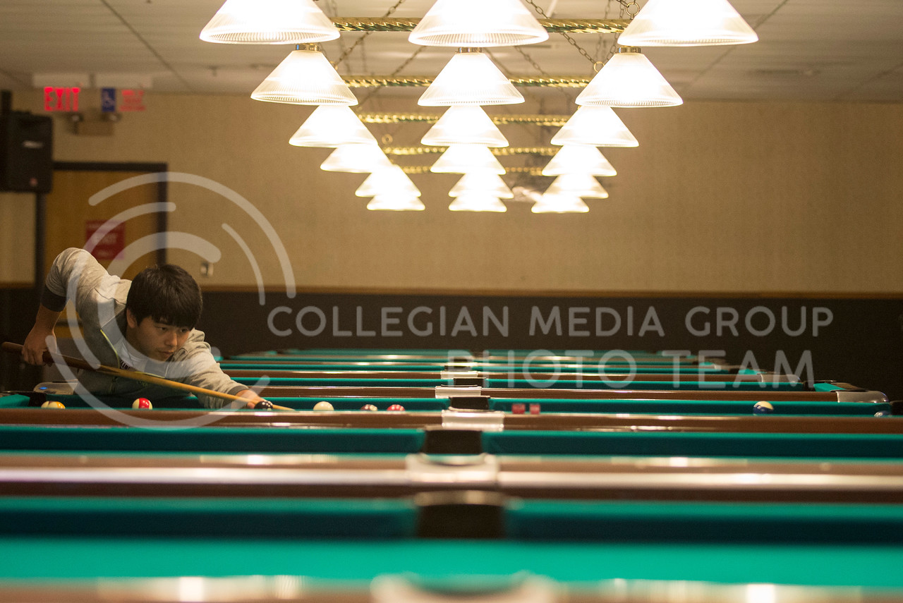 Anku MinXian Chen, freshman in computer science, lines up a shot while playing pool in the Union basement on Tuesday afternoon, Sept. 23, 2014. (Hannah Hunsinger | The Collegian)