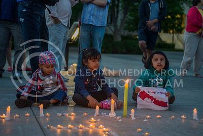 (Left to right) Ryan Pokharey, 3, Aayusha Aryal, 5, and Priyasa Couragain, 4, sit next to the lit candles during the candlelight vigil in Bosco Plaza on April 30, 2015. Many students, faculty, and community members came to remember and honor those affected by the earthquake. (George Walker | The Collegian)