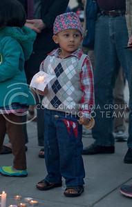 Ryan Pokharey, 3, holds a candle and a Nepal flag during the candlelight vigil in Bosco Plaza on April 30, 2015. (George Walker | The Collegian)