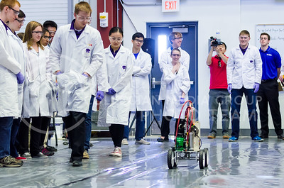 Ben Williams and Yichao Zhang, both juniors in chemical engineering, follow the pressure car team's car along the track as Aaron Akin, junior in biological systems engineering, watches from the starting line at the ChemE Car competition at KU Saturday. The pressure car subteam of the K-State ChemE Car team took first place at the regional competition. (Parker Robb   The Collegian)