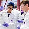 Chemical engineers Charlie Fu, senior, left, and Brett Bandy, sophomore, prepare a specific concentration of hydrochloric acid for the K-State team's battery-powered car at the AIChE regional ChemE Car competition Saturday at KU. (Parker Robb | The Collegian)