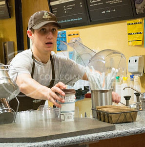 Matt Merriman, senior in secondary education, serves coffee to a customer at Caribou Coffee in the student union on January 20, 2014. (Cassandra Nguyen | The Collegian)