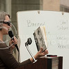 """Naomi Wood, English professor, shows illustrations from Shel Silverstein's book of poems and drawings """"Falling Up"""" during the banned book redin gin Bosco Plaza on Wednesday morning, Sept. 24, 2014. Silverstein's book was included in the event because some people believe the book teaches children to be rebellious and disrespectful.  (Hannah Hunsinger   The Collegian)"""